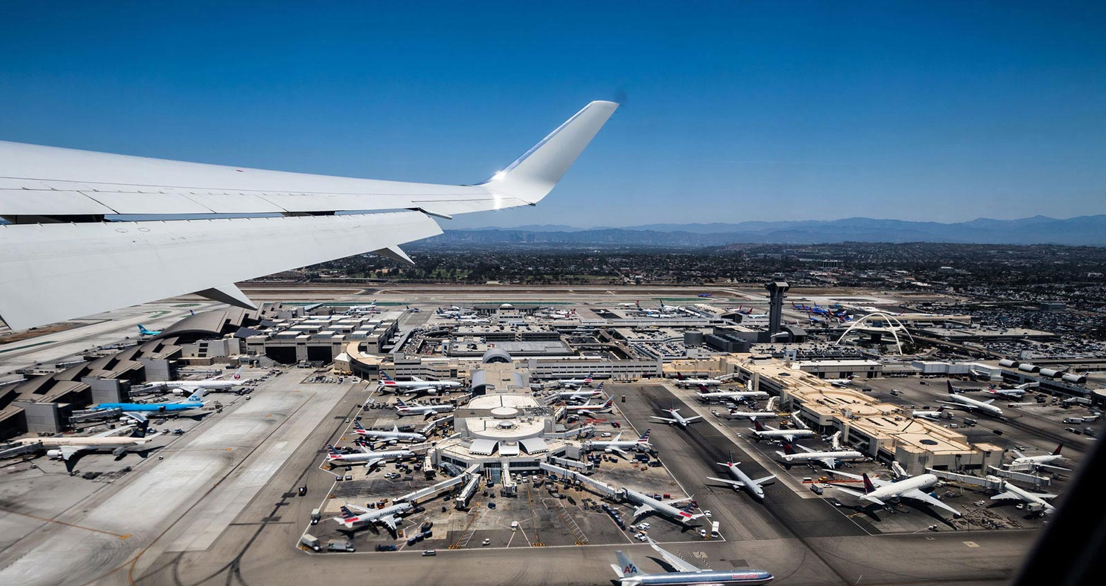 Background Image Showing Airplane wing flying over the terminals
