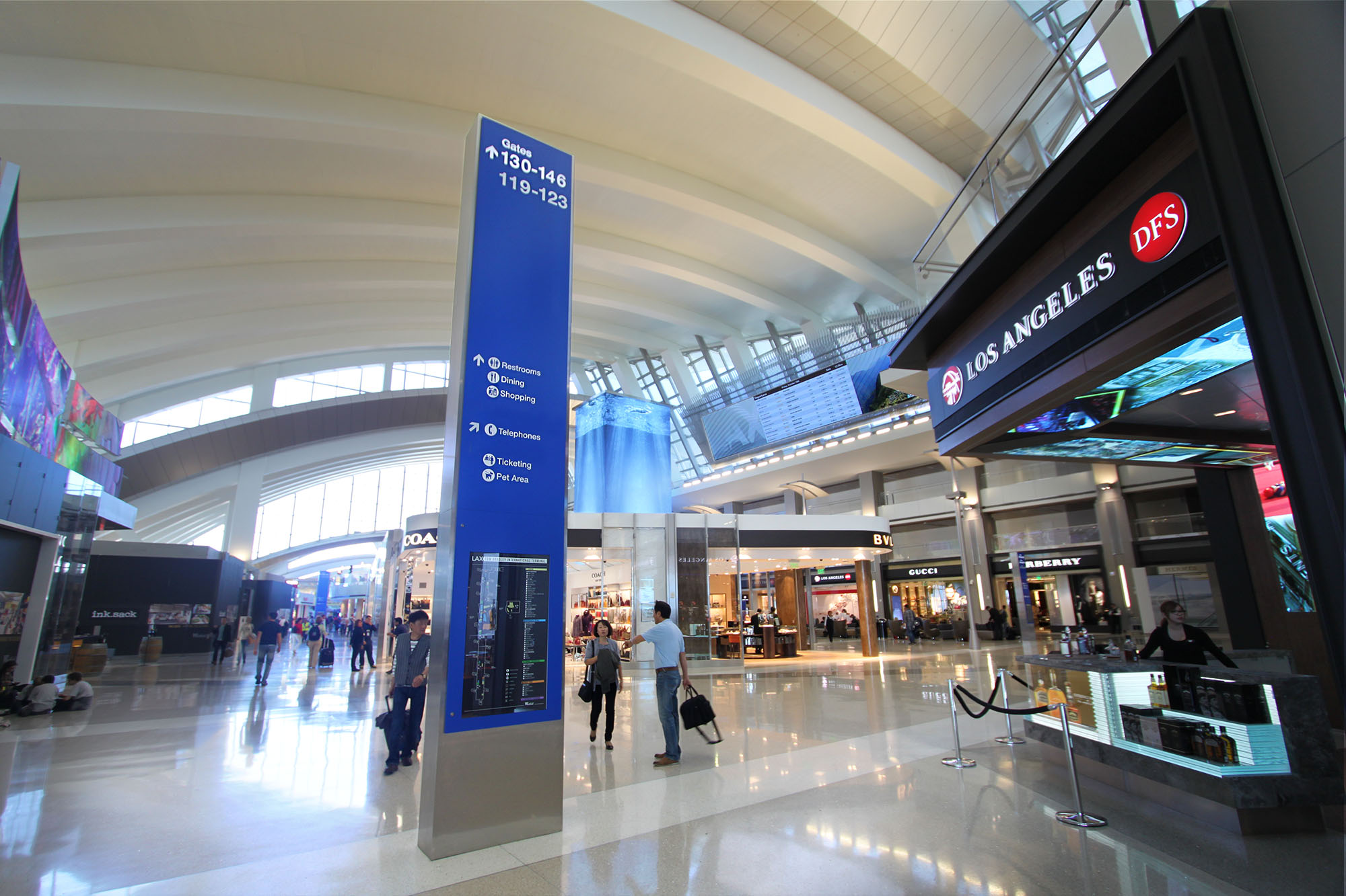 Inside Tom Bradley International Terminal showing travelers and shops